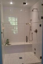 Glass shower enclosure with white tile