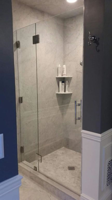 Glass shower door with blue walls by bryn mawr glass