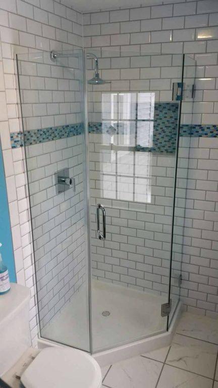 Framless glass shower door with blue tiles